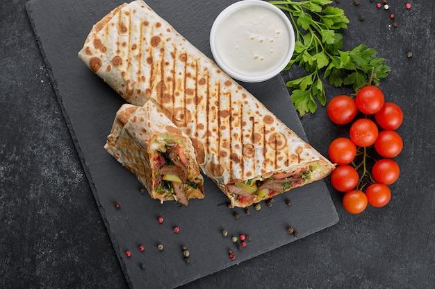 Shawarma à la viande, pan coupé, avec sauce, tomates, fromage, herbes et ail, sur ardoise noire