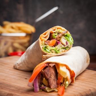Shawarma vue latérale avec pommes de terre frites dans une batterie de cuisine à bord