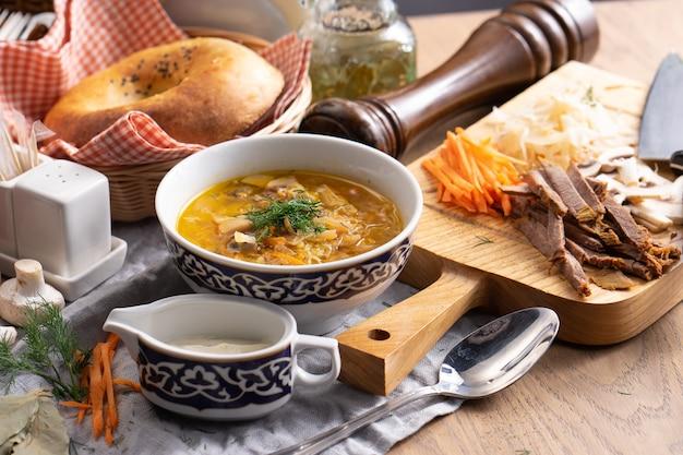 Shchi à la crème sure - une soupe de légumes traditionnelle russe faite de chou, pommes de terre, carottes et champignons dans une assiette avec un traditionnel ouzbek