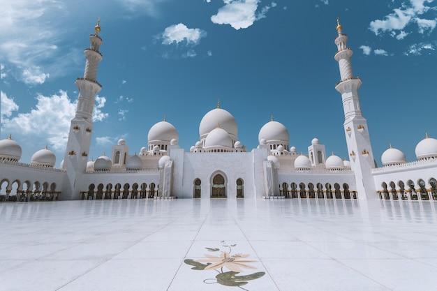 Sheikh zayed mosque à abu dhabi (eau) avec ciel bleu et nuages