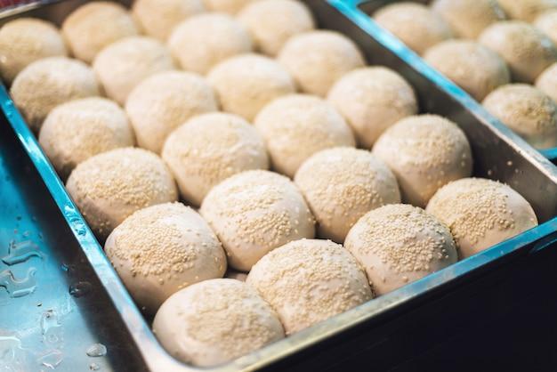 Sheng jian bao, petit pain de porc blanc nappé de sésame avant la friture.