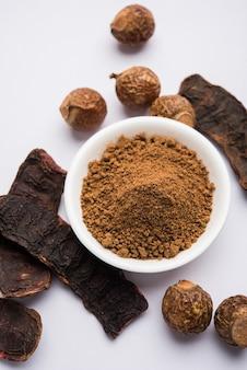 Shikakai cru séché et reetha ou poudre de noix de lavage dans un bol ou de l'huile essentielle, mise au point sélective