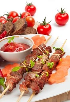Shish kebab aux herbes sur une plaque blanche avec tomates et sauce