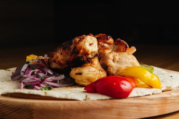 Shish kebab aux légumes sur planche de bois. poulet shashlik.