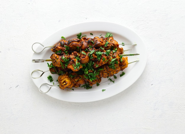 Shish kebab sur des brochettes servies sur une plaque blanche sur une vue de dessus blanche