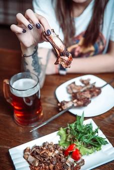 Shish kebab dans les mains des femmes à une table avec de la bière dans un café.