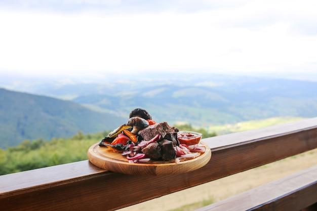 Shish kebab sur une planche de bois sur fond de montagnes.