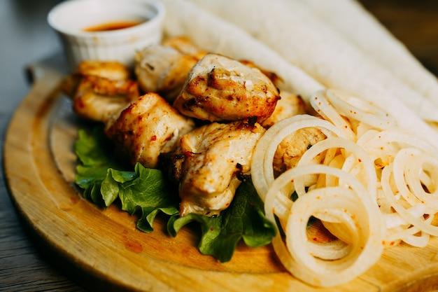 Shish kebab avec rondelle d'oignon et lavash sur la plaque de bois.