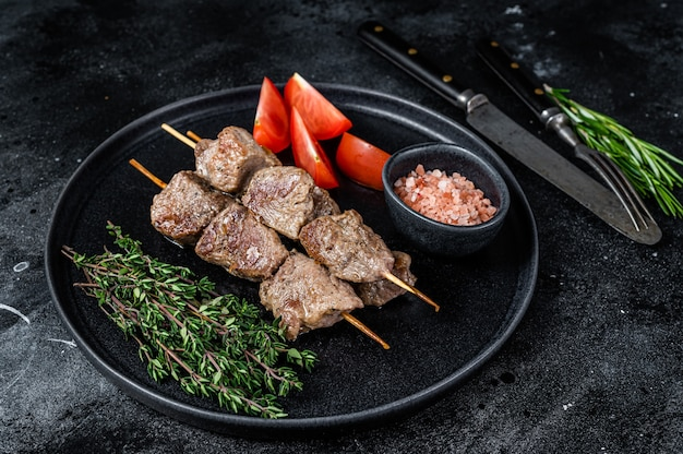 Shish kebabs viande et légumes grillés sur une assiette. table noire. vue de dessus.
