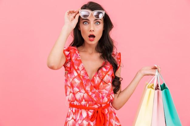 Shocked lady posant mur isolé tenant des sacs à provisions.