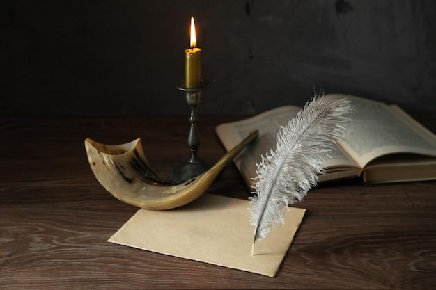 Shofar (corne), livre de la torah, bougie allumée, feuille de papier et stylo plume. fête juive de yom kippour