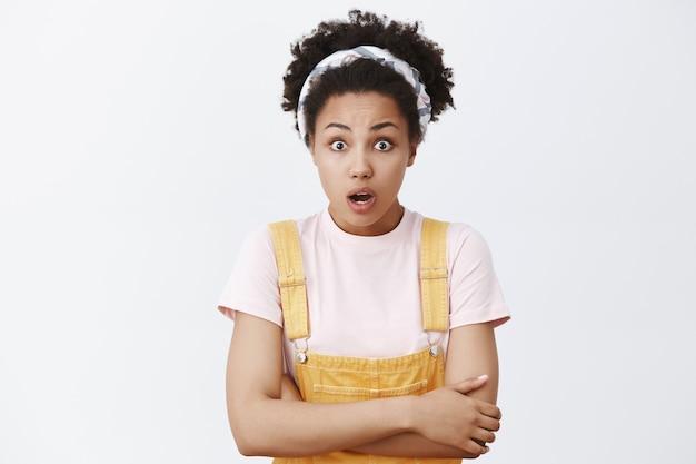 Shook impressionné fille afro-américaine en bandeau et salopette jaune, tenant les mains ensemble sur la poitrine et regardant