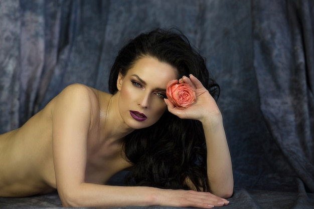 Shooting beauté du modèle brune sensuelle avec rose et posant avec les épaules nues