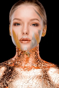 Shooting beauté d'une femme blonde de luxe avec un maquillage créatif et une feuille d'or sur ses épaules