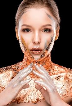 Shooting beauté d'un mannequin blond glamour avec maquillage créatif et feuille d'or sur les épaules et le visage