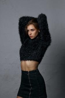 Shooting test pour une jeune mannequin glamour portant une jupe et un pull en jean