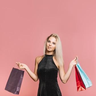 Shopper blonde souriante avec des sacs en papier
