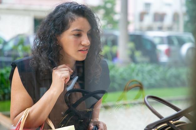 Shopper féminin focalisé regardant les accessoires dans la vitrine, tenant des sacs à provisions, debout au magasin à l'extérieur. vue de face à travers le verre. concept de magasinage de fenêtre