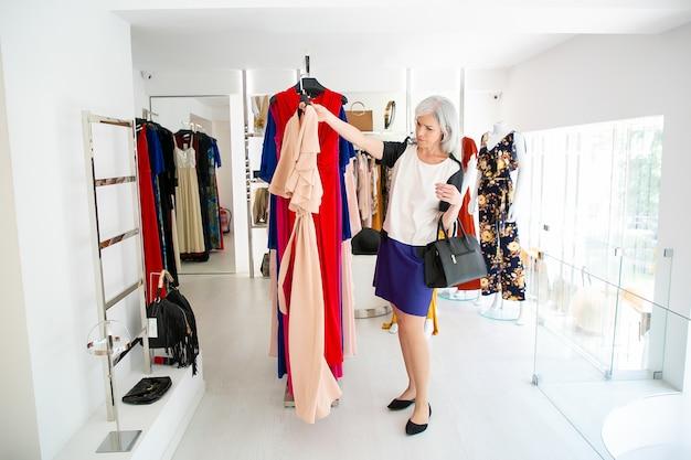 Shopper femme pensif choisissant une robe de soirée, prenant un cintre avec un chiffon pour essayer. femme faisant du shopping en magasin. concept de consommation