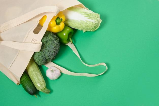 Shopper en tissu avec des légumes sur une surface verte concept de mode de vie écologique