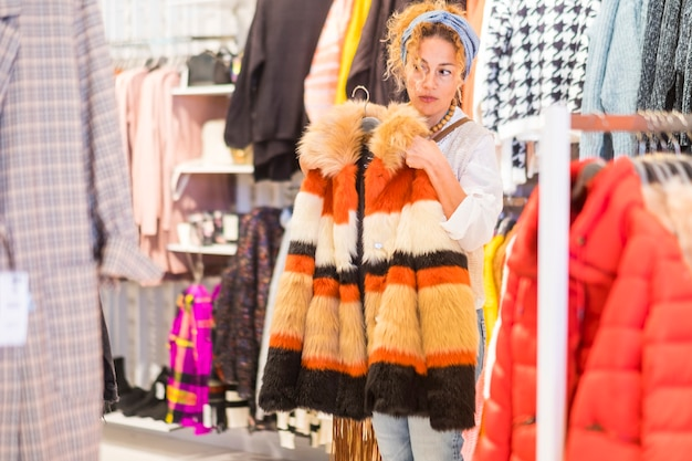 Shopping au magasin de vêtements de centre commercial pour une jolie femme caucasienne adulte