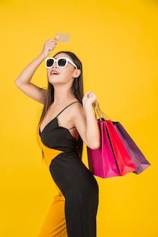 Shopping belle femme portant des lunettes avec une carte de crédit en or avec un sac en papier coloré sur un jaune.