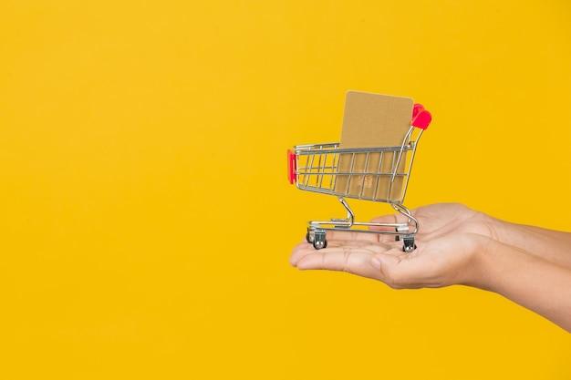 Shopping belle femme tenant un chariot à la main sur un jaune.