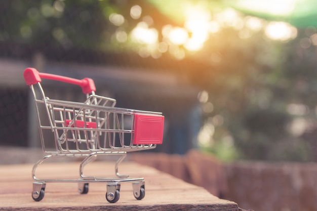 Shopping concept - caddie vide rouge sur une table en bois marron. les consommateurs en ligne peuvent faire leurs achats à domicile et en livraison. avec fond
