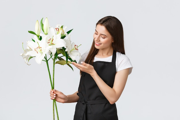 Shopping, employés et concept de petite entreprise. fleuriste tendre et mignon dans un magasin de fleurs faisant un bouquet parfait de lys blancs, touchant des feuilles et souriant heureux, traitant la commande en ligne, livre des fleurs.