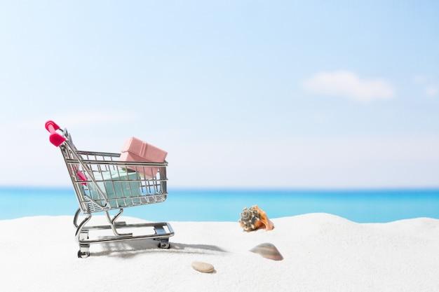 Shopping d'été. affaires et vente sur la plage. panier sur sable blanc