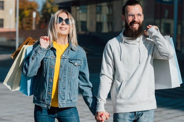 Shopping en famille. couple marchant avec des paquets le long de la rue dans le centre-ville.