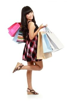 Shopping femme heureuse souriant tenant des sacs à provisions isolés.