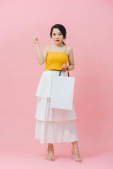 Shopping femme de mode souriante tenant des paquets blancs.