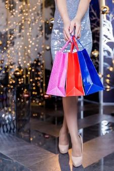 Shopping femme en robe portant des sacs à provisions. image de la moitié inférieure de la taille des jambes sexy en talons hauts et des sacs à provisions colorés, sur un mur festif.
