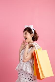Shopping femme tenant des sacs à provisions rose