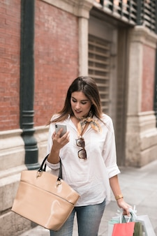 Shopping fille en regardant son téléphone portable