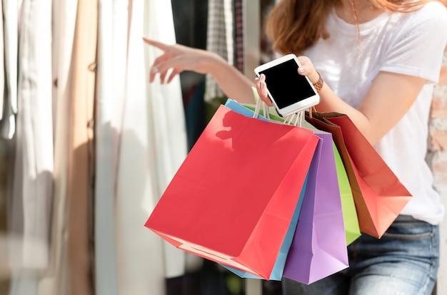 Shopping fille sac à provisions avec smartphone à la main.