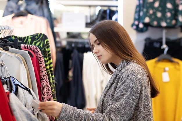 Shopping une jeune fille choisit des vêtements dans un magasin.