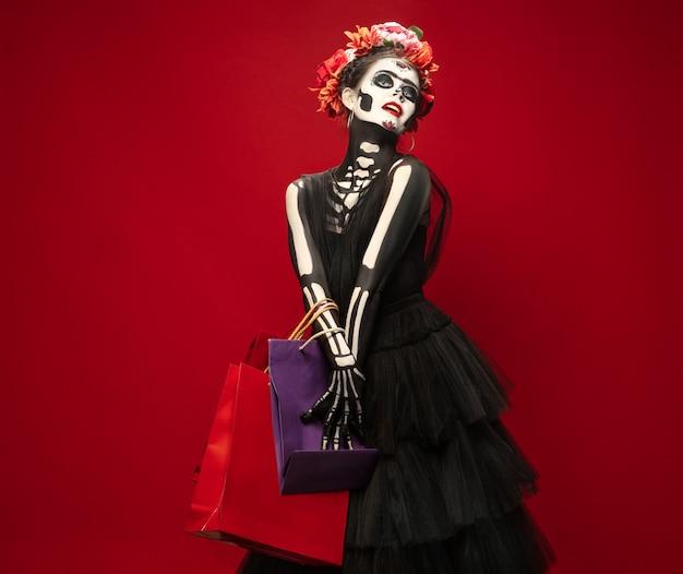 Shopping jeune fille comme la mort de santa muerte saint ou le crâne de sucre avec un maquillage lumineux