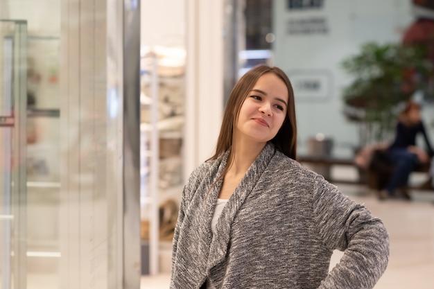 Shopping une jeune fille regarde les vitrines des magasins, sourit, fait des achats dans un centre commercial.