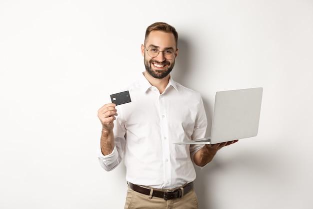 Shopping en ligne. bel homme montrant une carte de crédit et utilisant un ordinateur portable pour commander sur internet, debout sur fond blanc.