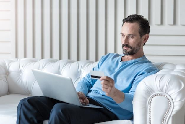 Shopping en ligne. bel homme séduisant ravi tenant un ordinateur portable et entrant les données de sa carte de crédit lors d'un achat en ligne