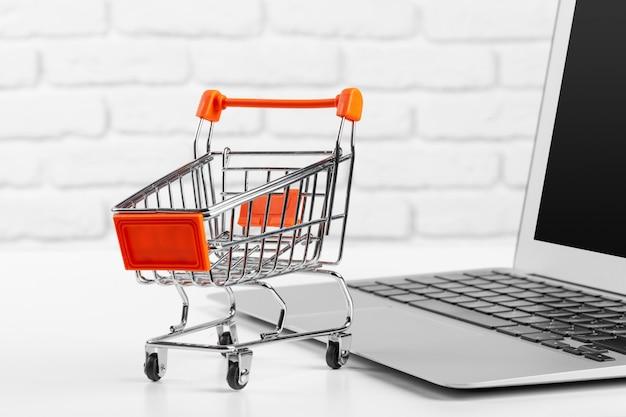 Shopping en ligne concept: mini panier et ordinateur portable