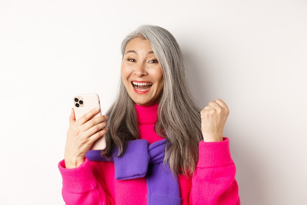 Shopping en ligne. gros plan d'une femme âgée asiatique joyeuse remportant un prix sur internet, tenant un smartphone et faisant une pompe à poing, debout sur fond blanc.
