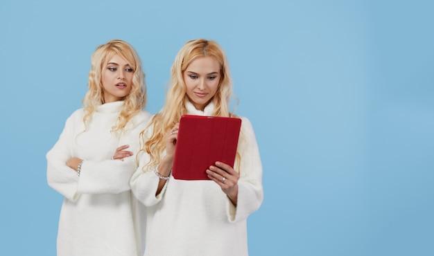 Shopping en ligne. jeunes modèles féminins font leurs achats à distance dans une boutique en ligne sur une tablette.