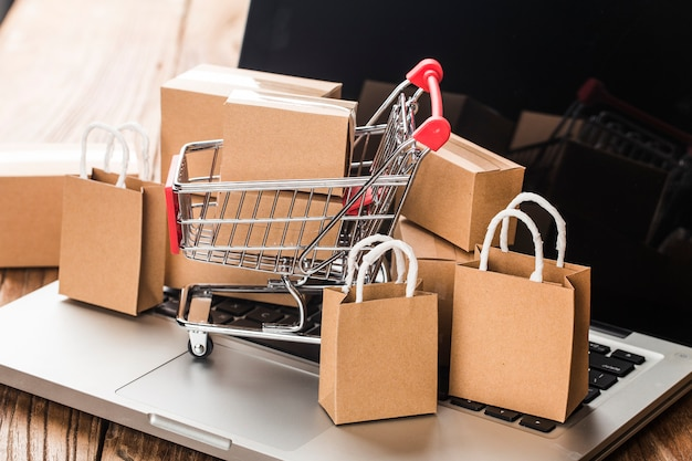 Shopping en ligne à la maison. cartons dans un panier sur un clavier d'ordinateur portable
