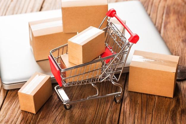 Shopping en ligne à la maison concept. cartons dans un panier sur un clavier d'ordinateur portable.