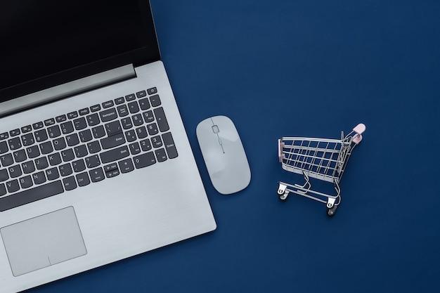 Shopping en ligne. ordinateur portable avec souris pc, chariot de supermarché sur fond bleu classique. couleur 2020. vue de dessus.