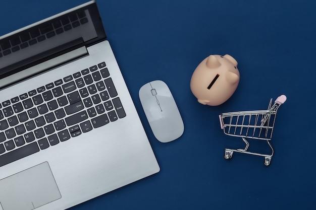 Shopping en ligne. ordinateur portable avec souris pc, chariot de supermarché et tirelire sur fond bleu classique. couleur 2020. vue de dessus.