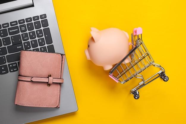 Shopping en ligne. ordinateur portable avec tirelire, chariot de supermarché, portefeuille sur jaune